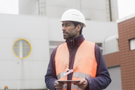 Man wearing reflective vest and hard hat holding tablet looking around - SGF02187