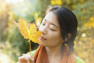 Close-up of young woman with closed eyes holding dry maple leaf at park on sunny day - FSIF01040