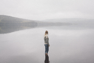 Woman standing in lake against sky during foggy weather, Jaervsoe, Haelsingland, Sweden - FSIF01058