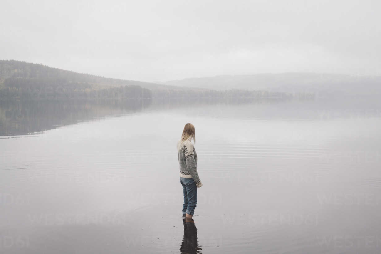 Woman standing in lake against sky during foggy weather, Jaervsoe, Haelsingland, Sweden - FSIF01058 - fStop/Westend61