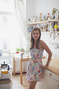 Portrait of beautiful woman standing by counter in kitchen at home - FSIF01067