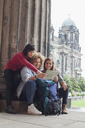 Young female tourists reading map at Altes Museum against Berlin Cathedral, Germany - FSIF01088