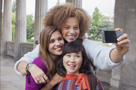 Smiling young woman taking selfie with female friends - FSIF01100