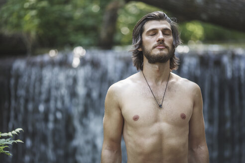 Shirtless young man with closed eyes standing against waterfall at forest - FSIF01106