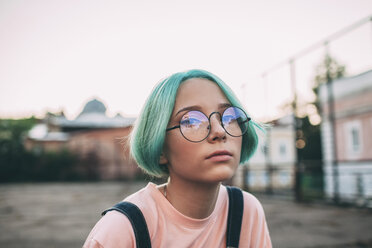 Portrait of teenage girl with green dyed hair wearing eyeglasses - FSIF01121