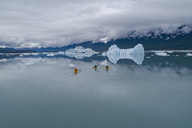People canoeing in glacier lagoon against cloudy sky, Knik Glacier, Palmer, Alaska, USA - FSIF01127