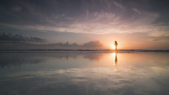 Silhouette woman at sea shore against cloudy sky during sunset, Daytona, Florida, USA - FSIF01157