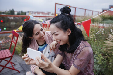 Happy woman looking at female friend using smart phone on patio - FSIF01172