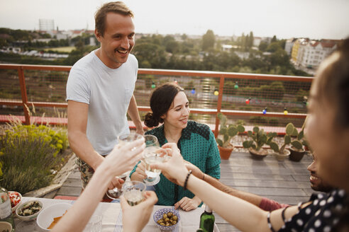 Happy male and female friends toasting wineglasses on patio - FSIF01175