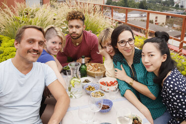 Portrait of happy male and female friends sitting at outdoor table at patio - FSIF01181