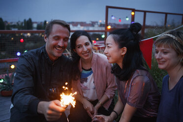 Happy man holding sparkler while sitting with female friends at night - FSIF01184