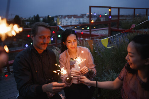 Male and female friends holding sparklers on patio - FSIF01187