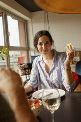 Smiling woman holding bread while looking at man in house - FSIF01190