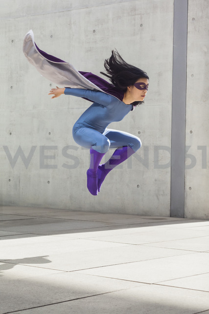 Female superhero levitating in mid-air against wall - FSIF01196 - fStop/Westend61