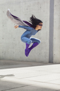 Female superhero levitating in mid-air against wall - FSIF01196