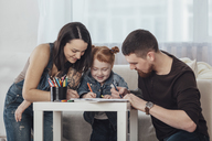 Parents drawing with daughter while resting in living room at home - FSIF01214