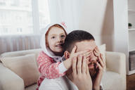 Daughter covering father's eyes while playing in living room at home - FSIF01217