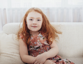 Portrait of smiling girl with redhead sitting on sofa at home - FSIF01220