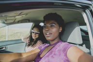 Young woman sitting with female friend looking away while sitting in car on sunny day - FSIF01250