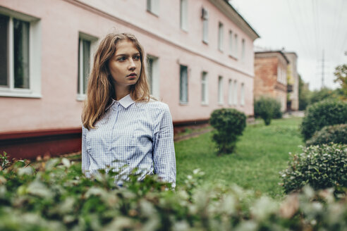 Thoughtful teenage girl standing by plants against building - FSIF01262