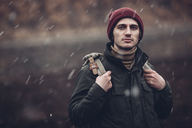 Portrait of man carrying backpack while standing outdoors during snowfall - FSIF01271
