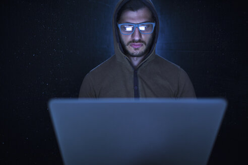 Serious computer hacker wearing hooded shirt using laptop against black background - FSIF01283