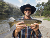 Portrait of happy mature man holding fish by river, Jindabyne, New South Wales, Australia - FSIF01335