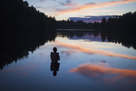 Rear view of shirtless boy in lake during sunset - FSIF01344