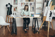 Beautiful female design professional working at workbench in studio - FSIF01347