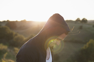 Side view of man wearing hooded jacket on field during sunny day - FSIF01353