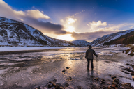 United Kingdom, Scotland, Highlands, female hiker standing at icy riverside - SMAF00936