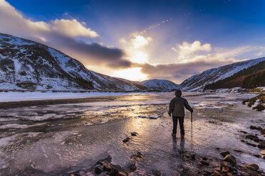 United Kingdom, Scotland, Highlands, female hiker standing at icy riverside - SMAF00936