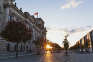 Germany, Berlin, Regierungsviertel, Reichstag building with German flags and Paul-Loebe-Building at sunset - GWF05432