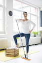 Portrait of confident woman at home wiping the floor - MOEF00798