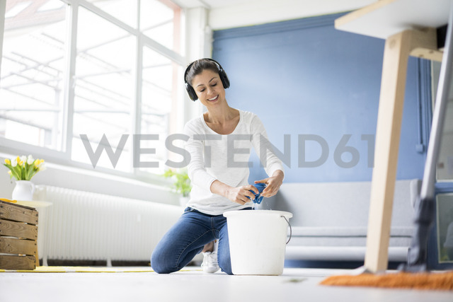Smiling woman at home wearing headphones wiping the floor - MOEF00801