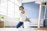 Smiling woman at home wearing headphones wiping the floor - MOEF00801