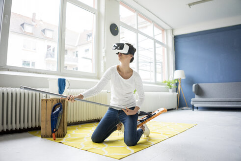 Vital woman at home wearing VR glasses wiping the floor - MOEF00804