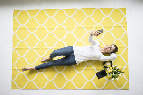 Smiling woman holding cell phone lying on carpet with bunch of tulips - MOEF00807