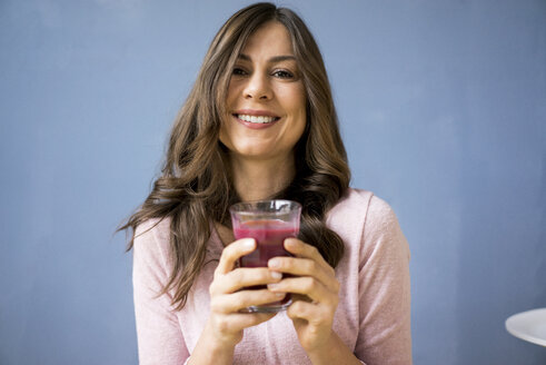 Portrait of smiling woman holding glass of juice - MOEF00816