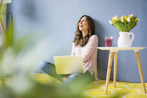 Happy woman sitting on floor with laptop - MOEF00819