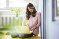 Smiling woman sitting on floor using laptop - MOEF00822