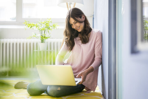 Smiling woman sitting on floor using laptop - MOEF00822