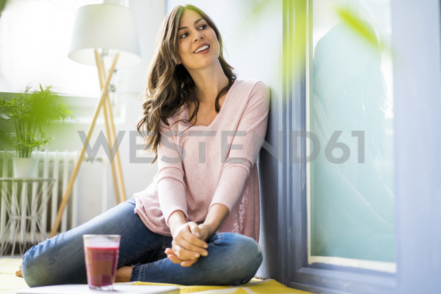 Smiling woman sitting on floor with glass of juice - MOEF00825