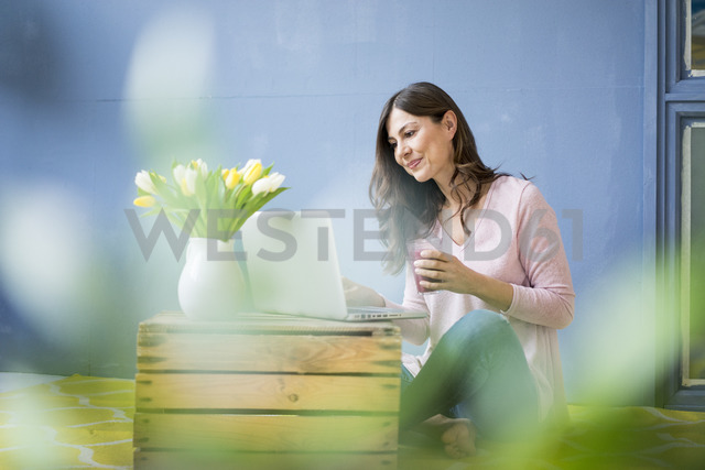 Woman sitting on floor with glass of juice using laptop - MOEF00828