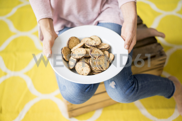 Woman holding a plate with cakes - MOEF00831