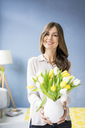 Portrait of smiling woman holding bunch of tulips in a jar - MOEF00843