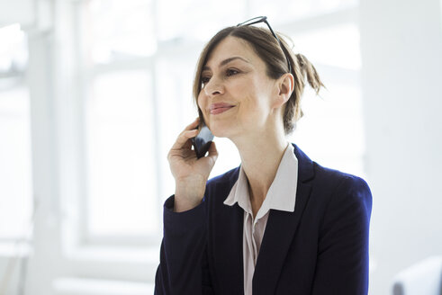 Portrait of smiling businesswoman on cell phone - MOEF00846