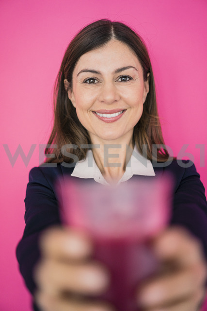 Portrait of smiling businesswoman in front of pink wall holding glass of juice - MOEF00852