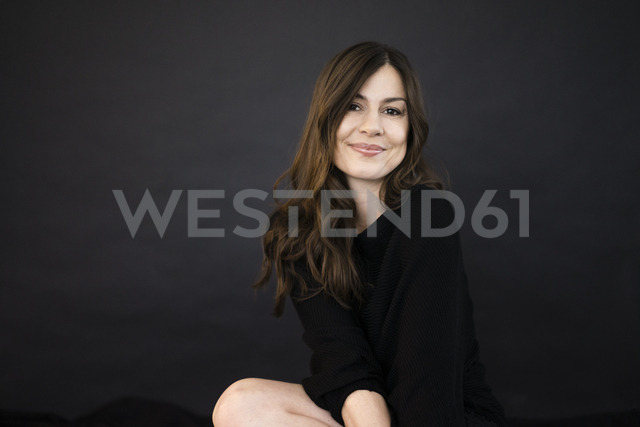 Portrait of smiling woman in front of black wall - MOEF00855