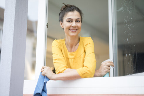 Portrait of smiling woman cleaning the window - MOEF00858